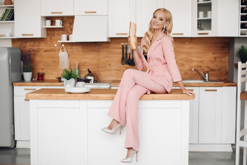 Πανέμορφη ξανθή γυναίκα στο ρόδινο κοστούμι με τη φραντζόλα του ψωμιού στο countrer κουζινών στοκ εικόνες