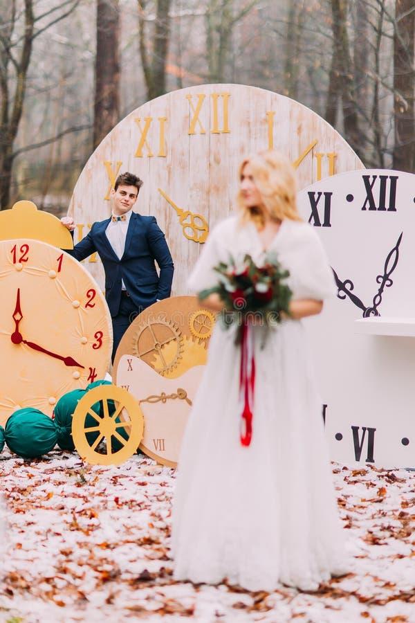 Πανέμορφη ξανθή νύφη με την ανθοδέσμη στη δασική σκιαγραφία φθινοπώρου του νεόνυμφου στο υπόβαθρο στοκ εικόνα