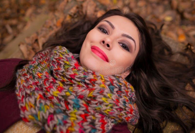 Πανέμορφη ρομαντική νέα γυναίκα με την όμορφη μακριά καφετιά τρίχα, που ξαπλώνει στο δάσος φθινοπώρου, που χαμογελά λεπτά στοκ εικόνες