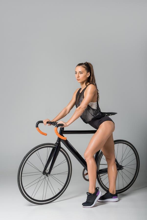 πανέμορφη σαγηνευτική νέα γυναίκα που στέκεται με το ποδήλατο και που κοιτάζει μακριά στοκ φωτογραφία με δικαίωμα ελεύθερης χρήσης