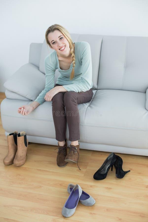 Πανέμορφη χαμογελώντας γυναίκα που δένει τα κορδόνια της που κάθονται στον καναπέ στοκ φωτογραφία με δικαίωμα ελεύθερης χρήσης