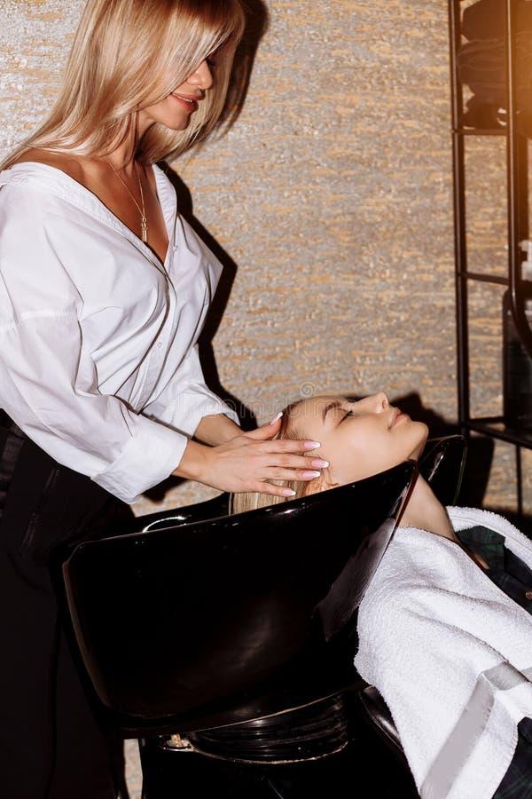 Πανέμορφη χαριτωμένη νέα γυναίκα που απολαμβάνει το επικεφαλής μασάζ ενώ επαγγελματικός κομμωτής που εφαρμόζει το σαμπουάν η τρίχ στοκ φωτογραφίες