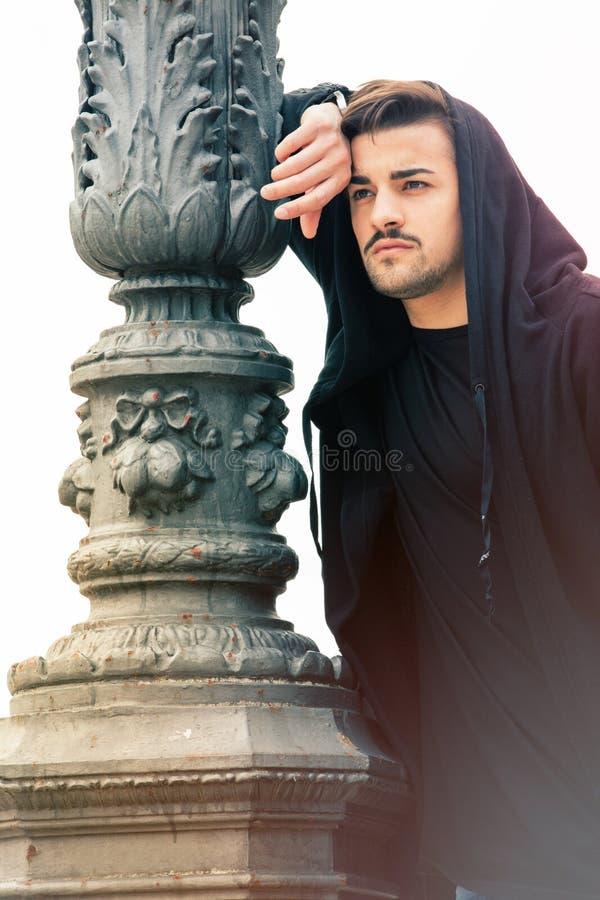 Πανέμορφος νεαρός άνδρας που κλίνει ενάντια σε ένα παλαιό lamppost στοκ εικόνες