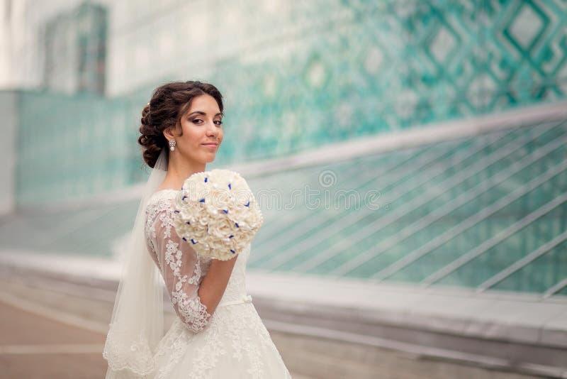 Πανέμορφος νύφη με ένα διάστημα αντιγράφων στο σύγχρονο υπόβαθρο αρχιτεκτονικής στοκ φωτογραφία