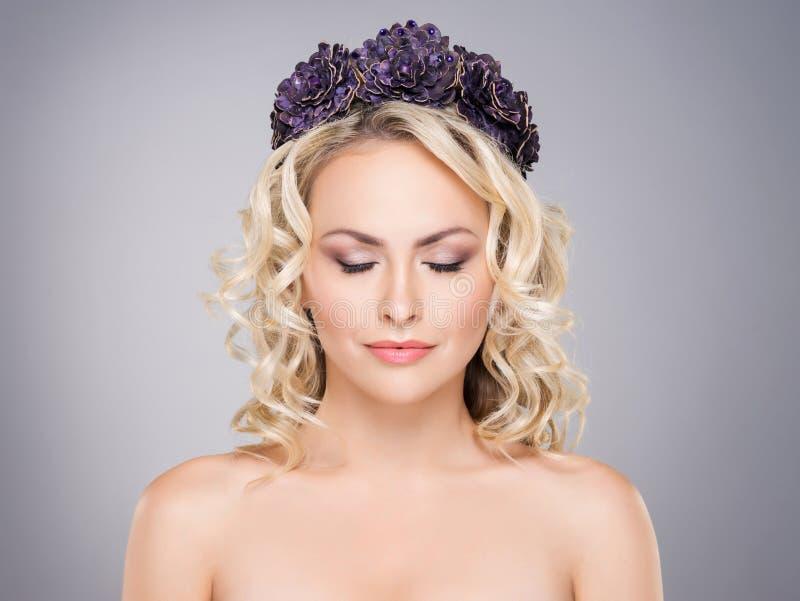 Πανέμορφος ξανθός με τις ιδιαίτερες προσοχές που φορούν μια πορφυρή κορώνα λουλουδιών στοκ φωτογραφία