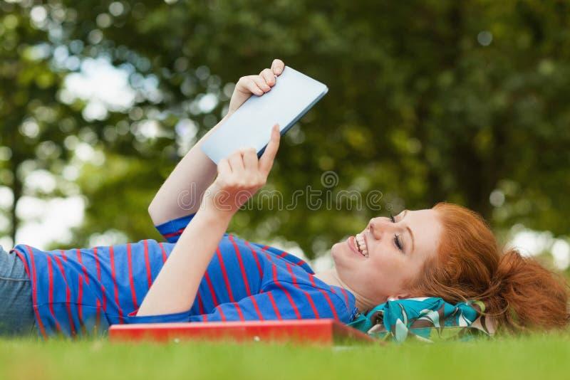 Πανέμορφος χαμογελώντας σπουδαστής που βρίσκεται στη χλόη που χρησιμοποιεί την ταμπλέτα στοκ φωτογραφίες