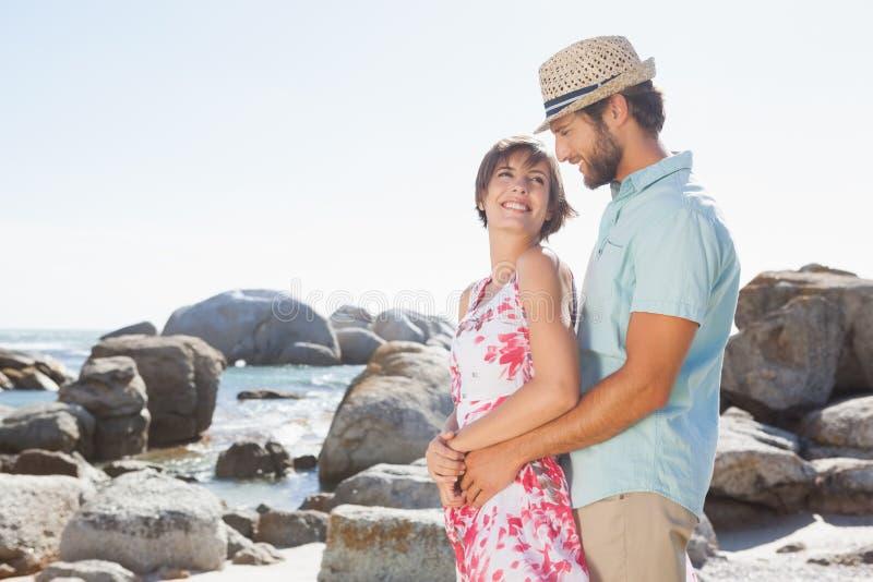 Πανέμορφο ζεύγος που αγκαλιάζει από την ακτή στοκ εικόνα με δικαίωμα ελεύθερης χρήσης