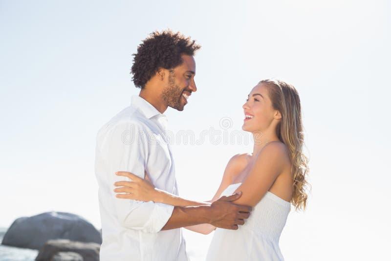 Πανέμορφο ζεύγος που αγκαλιάζει στην ακτή στοκ φωτογραφία