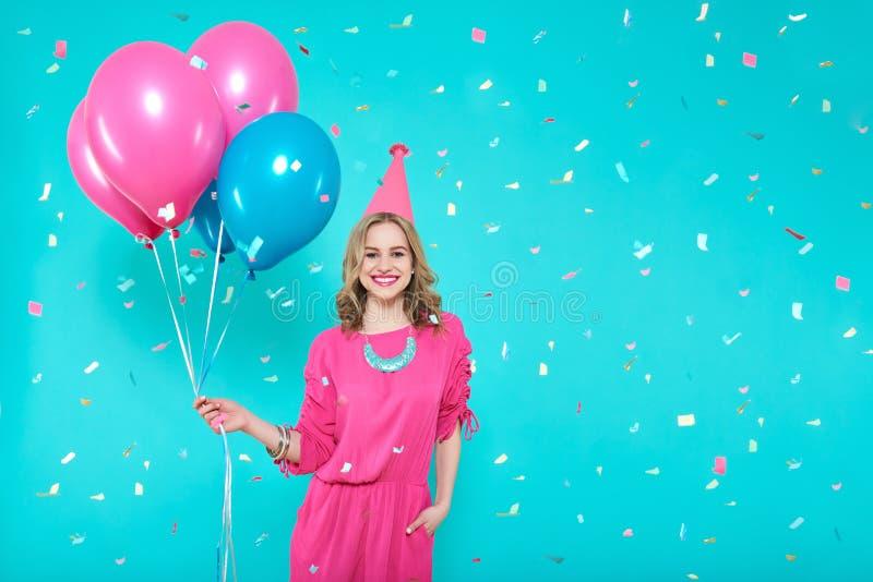 Πανέμορφο κορίτσι γενεθλίων στην εξάρτηση κομμάτων που κρατά τα ζωηρόχρωμα μπαλόνια Ελκυστικά καθιερώνοντα τη μόδα γενέθλια εορτα στοκ εικόνες