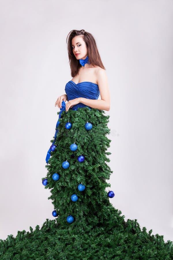 Πανέμορφο κορίτσι με το χριστουγεννιάτικο δέντρο ως φόρεμα στην έννοια μόδας στοκ φωτογραφία
