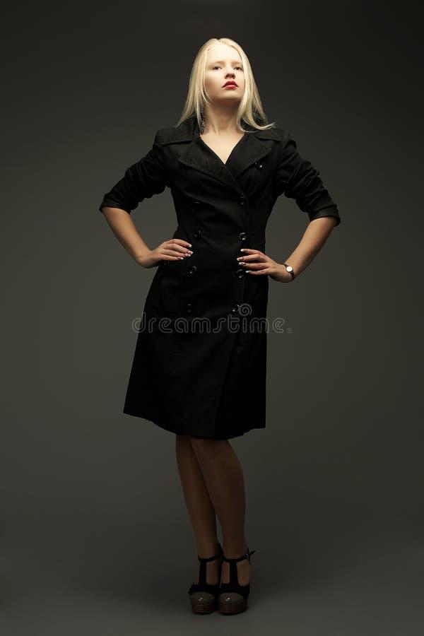 Πανέμορφο πρότυπο μόδας στη μαύρη στάση παλτών στοκ εικόνες