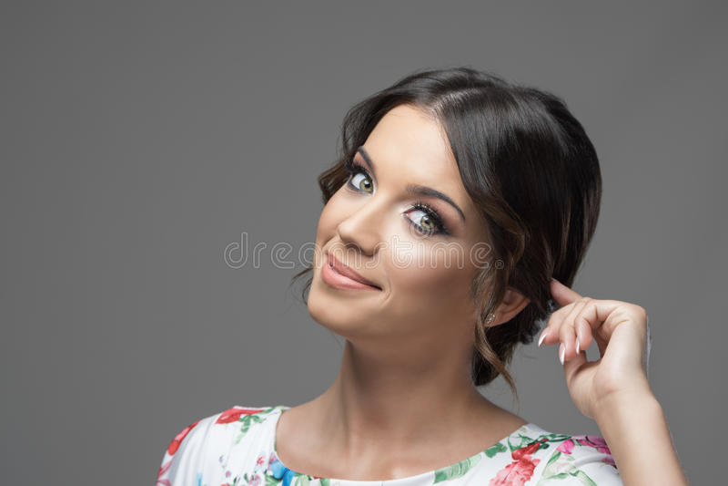 Πανέμορφο πρότυπο ομορφιάς με τα μάτια smokey makeup που παίζουν με την κλειδαριά τρίχας που χαμογελά στη κάμερα στοκ εικόνες