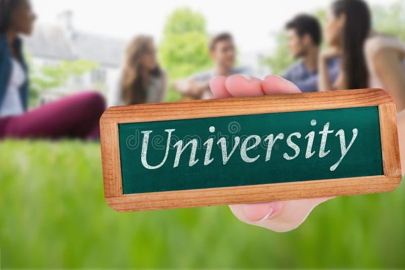 Πανεπιστήμιο ενάντια στους ευτυχείς σπουδαστές που κάθονται έξω στην πανεπιστημιούπολη στοκ φωτογραφία με δικαίωμα ελεύθερης χρήσης