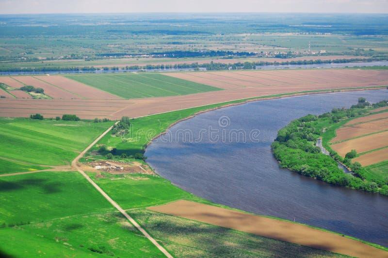 Πανοραμική άποψη από το αεροπλάνο στο φυσικό τοπίο: ο ποταμός, οι τομείς, η πόλη στοκ εικόνες