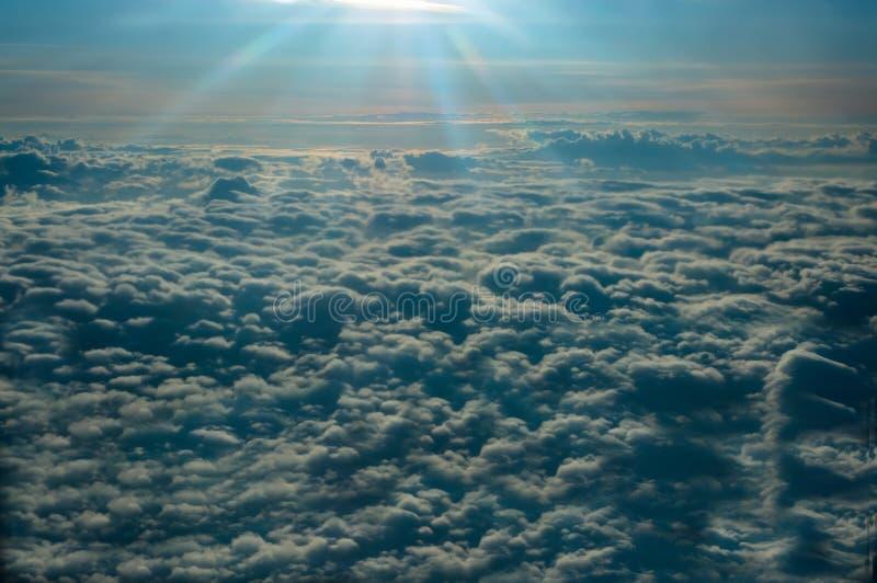 Πανοραμική άποψη από το παράθυρο του αεροπλάνου που πετά επάνω από τα ήλιος-βρεγμένα σύννεφα στοκ εικόνα