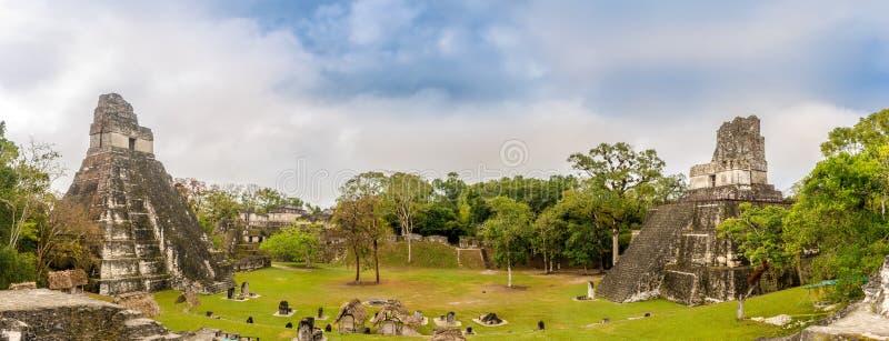 Πανοραμική άποψη στη μεγάλη θέση με το ναό Ι και το ναό ΙΙ στο εθνικό πάρκο Tikal - Γουατεμάλα στοκ εικόνες