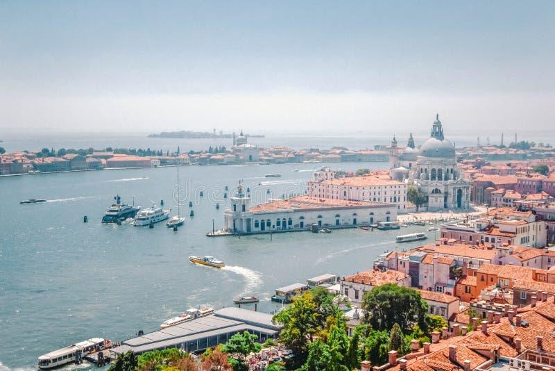 Πανοραμική άποψη της Βενετίας - μεγάλο κανάλι με τις γόνδολες, το χαιρετισμό della της Σάντα Μαρία βασιλικών και τις κόκκινες κερ στοκ φωτογραφία με δικαίωμα ελεύθερης χρήσης