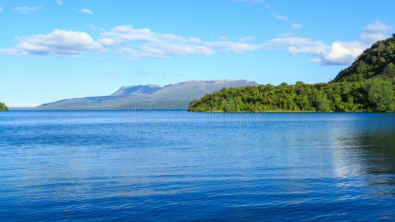 Πανοραμική άποψη της λίμνης Tarawera, Νέα Ζηλανδία, με το υποστήριγμα Tarawera στο υπόβαθρο στοκ φωτογραφία