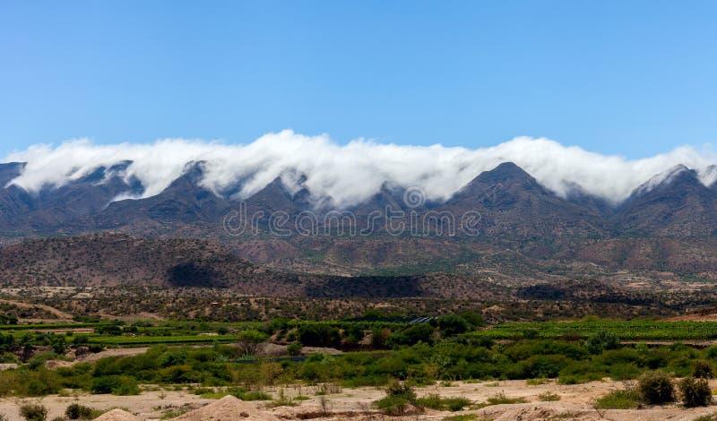 Πανοραμική άποψη της οροσειράς της Βολιβίας Τα σύννεφα χύνουν πέρα από τις σειρές και την κατάρρευση βουνών στην κοιλάδα στοκ εικόνες