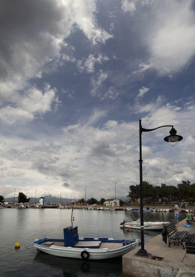 Πανοραμική άποψη του αλιευτικού σκάφους σε ένα ηλιόλουστο απόγευμα στο ήρεμο Αιγαίο πέλαγος στην προκυμαία της πόλης παραλιών Nea στοκ φωτογραφίες