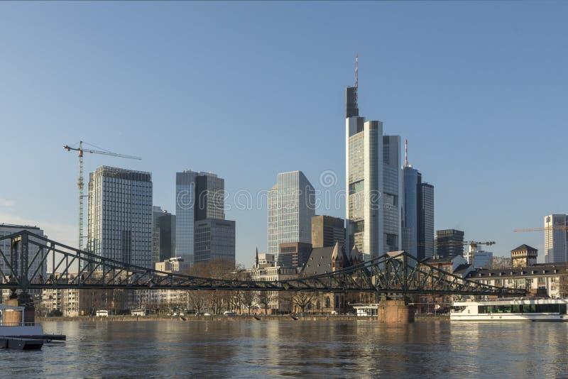 Πανοραμική άποψη του ορίζοντα της Φρανκφούρτης με την παλαιά γέφυρα ποδιών σιδήρου στοκ φωτογραφίες