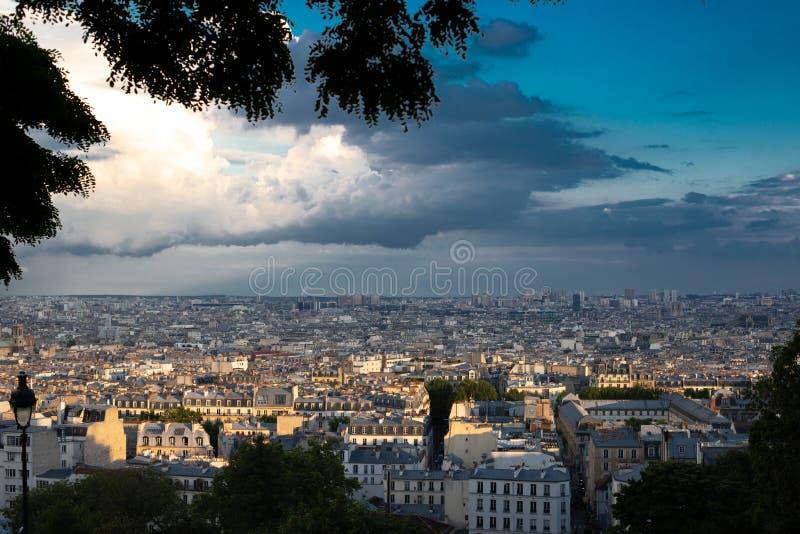 Πανοραμική άποψη του Παρισιού που φωτίζεται από τον ήλιο μετά από μια καταιγίδα Άποψη από το λόφο Montmartre του Παρισιού το βράδ στοκ εικόνα