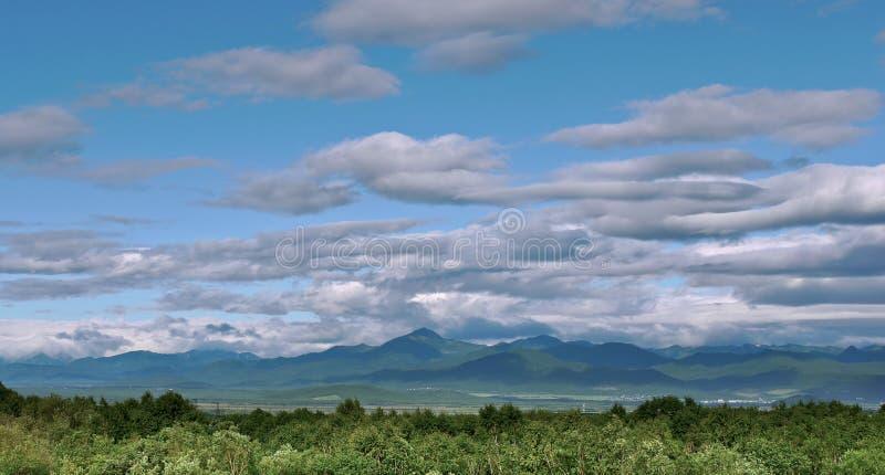 Πανοραμική άποψη των όμορφων σύννεφων πέρα από μια πράσινη κοιλάδα λόφων στοκ εικόνες