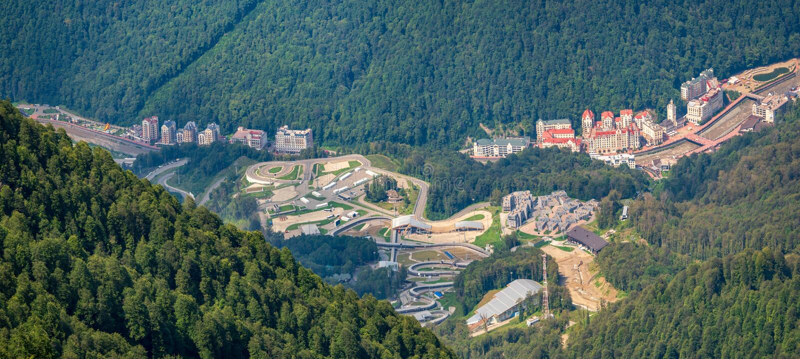 Πανοραμική θερινή άποψη από την κορυφή της σειράς Aibga στο χιονοδρομικό κέντρο της Rosa Khutor με τα χαρακτηρισμένα ξενοδοχεία στοκ φωτογραφία