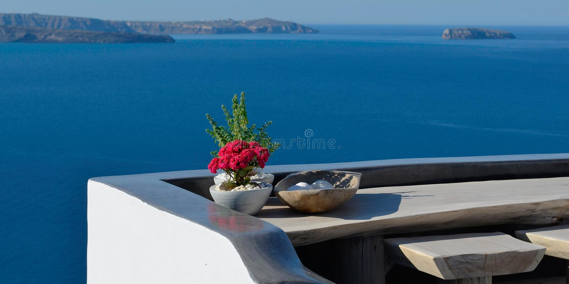 Πανοραμικό πεζούλι με το κόκκινο λουλούδι στον πίνακα Παράβλεψη Caldera Oia, Santorini, Ελλάδα στοκ εικόνα