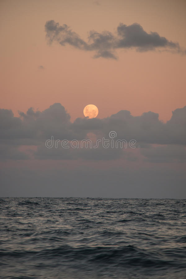 Πανσέληνος πέρα από τον ωκεανό και τα σύννεφα στοκ εικόνα