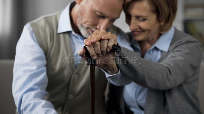 Παντρεμένοι πρεσβύτερος άνθρωποι που κάθονται μαζί να κρατήσει τα χέρια στο ραβδί περπατήματος, στενότητα στοκ φωτογραφία