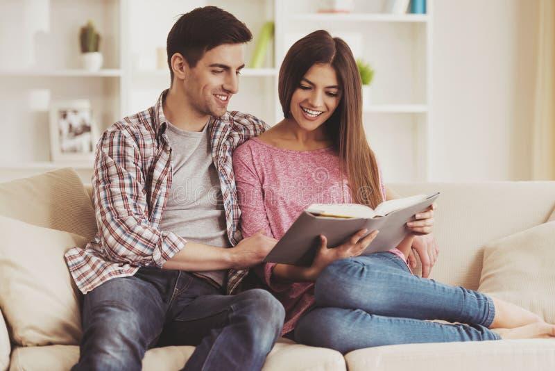 Παντρεμένος στο βιβλίο ανάγνωσης καναπέδων στοκ εικόνες