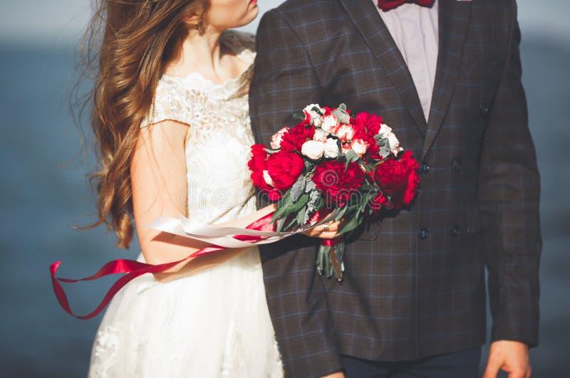 Παντρεμένο γαμήλιο ζευγάρι που στέκεται σε μια αποβάθρα πέρα από τη θάλασσα στοκ εικόνες