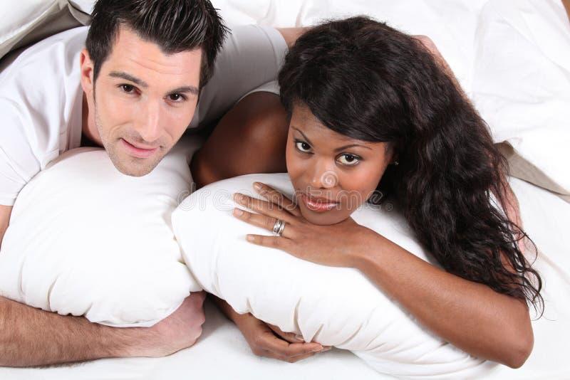 Παντρεμένο ζευγάρι που βρίσκεται στο κρεβάτι στοκ φωτογραφία με δικαίωμα ελεύθερης χρήσης