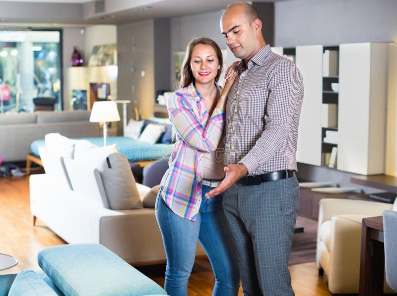 Παντρεμένο ζευγάρι που ψάχνει το νέο μοντέρνο καναπέ στοκ φωτογραφία