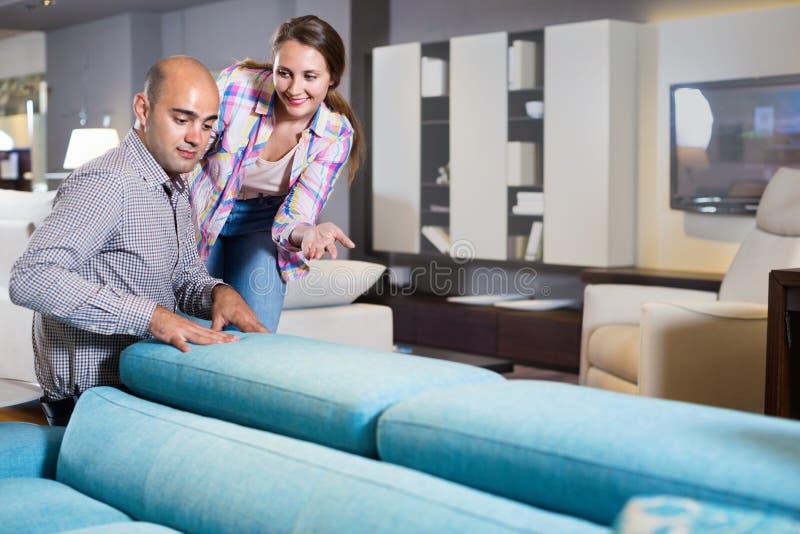 Παντρεμένο ζευγάρι που ψάχνει το νέο μοντέρνο καναπέ στοκ φωτογραφίες