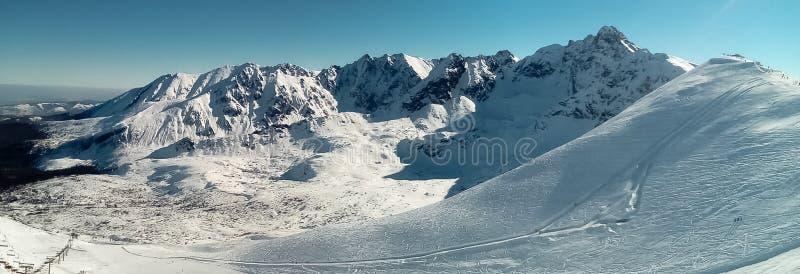 Πανόραμα βουνών με το χιόνι και το μπλε ουρανό στοκ φωτογραφία με δικαίωμα ελεύθερης χρήσης