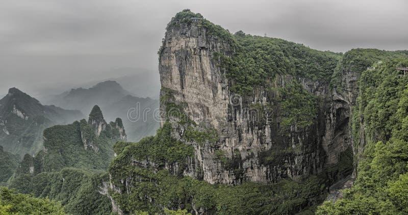 Πανόραμα: Δραματική καλλιτεχνική άποψη της αιχμής βουνών Tianmen με μια άποψη της σπηλιάς γνωστής ως πύλη ουρανού ` s που περιβάλ στοκ εικόνα με δικαίωμα ελεύθερης χρήσης