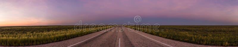 πανόραμα ενός ευθύ δρόμου μέσω του εσωτερικού της Αυστραλίας, μετά από ένα όμορφο ηλιοβασίλεμα, Βόρεια Περιοχή στοκ εικόνες