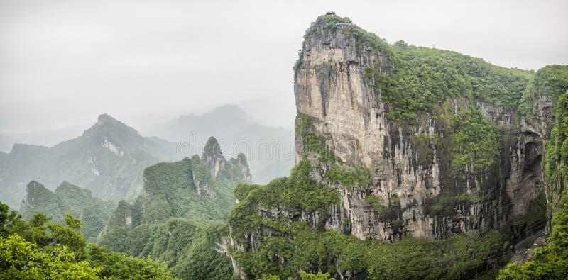 Πανόραμα της αιχμής βουνών Tianmen με μια άποψη της σπηλιάς γνωστής ως πύλη ουρανού ` s που περιβάλλεται από το πράσινες δάσος κα στοκ φωτογραφίες με δικαίωμα ελεύθερης χρήσης