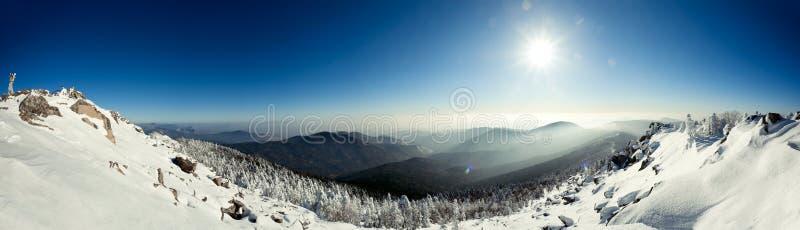 Πανόραμα του τοπίου βουνών χιονιού με το μπλε ουρανό στοκ φωτογραφία