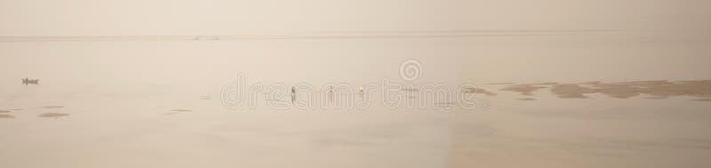 Πανόραμα των ανθρώπων που περπατούν στις τράπεζες άμμου στον ποταμό του Γάγκη και ένα άτομο που αλιεύουν, όλα από μακριά στοκ εικόνες
