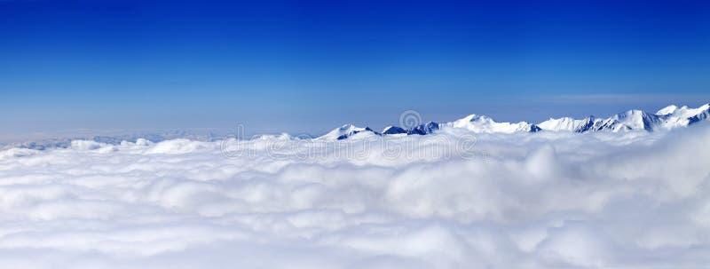 Πανόραμα των βουνών κάτω από τα σύννεφα στη συμπαθητική ημέρα ήλιων στοκ εικόνες