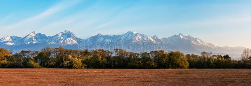 Πανόραμα των βουνών, του τομέα και του μπλε ουρανού στοκ εικόνες με δικαίωμα ελεύθερης χρήσης