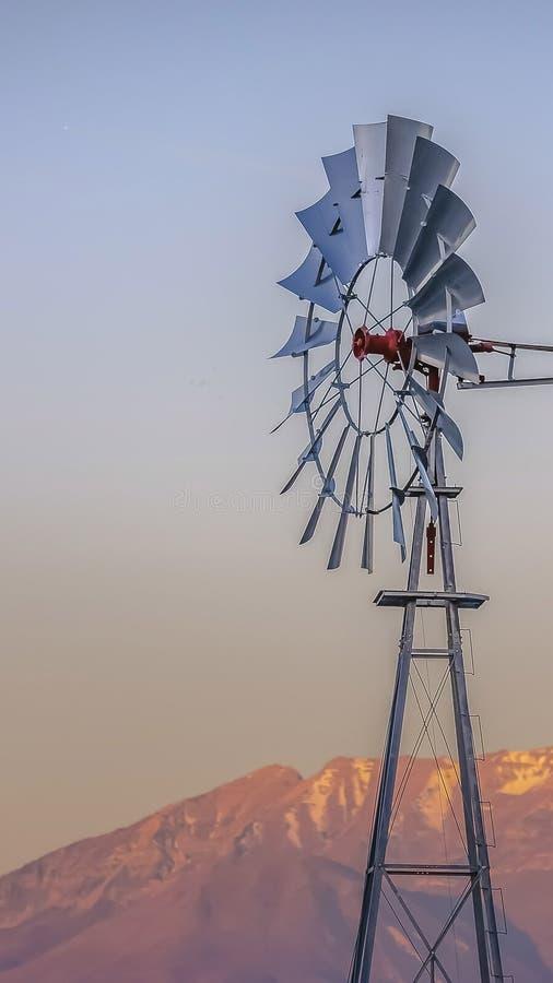 Πανόραμα Windpump με ένα τραχύ χρυσό βουνό και ένα νεφελώδες υπόβαθρο ουρανού στοκ φωτογραφία με δικαίωμα ελεύθερης χρήσης