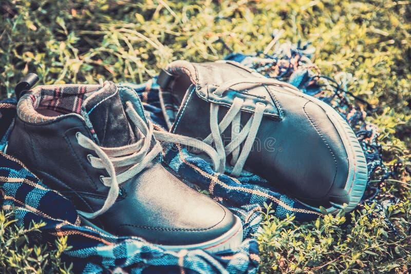 Παπούτσια ατόμων στη χλόη που τυλίγεται σε ένα μαντίλι στοκ εικόνες