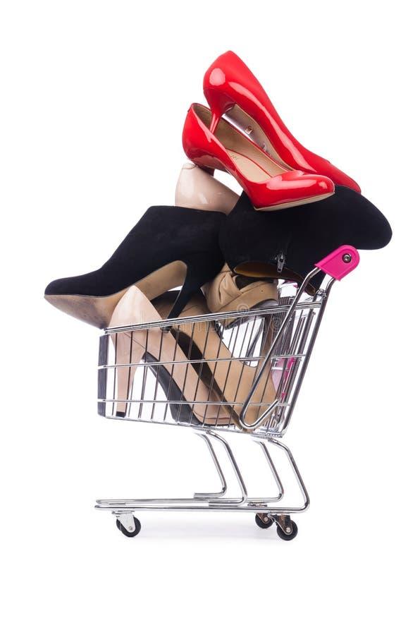 Παπούτσια γυναικών στο κάρρο αγορών στο λευκό στοκ εικόνες