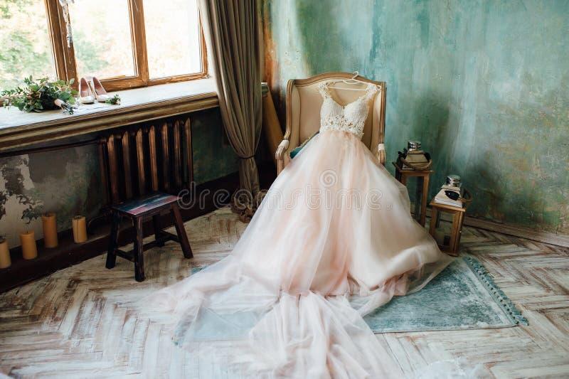 Παπούτσια και γαμήλιο φόρεμα στην καρέκλα στο δωμάτιο στοκ εικόνα