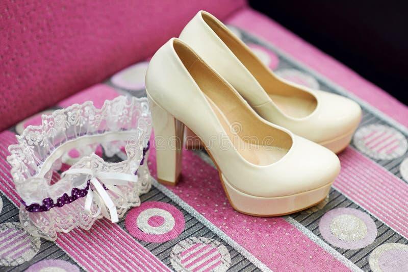 Παπούτσια και garter νυφών στον ξύλινο πίνακα στοκ φωτογραφία