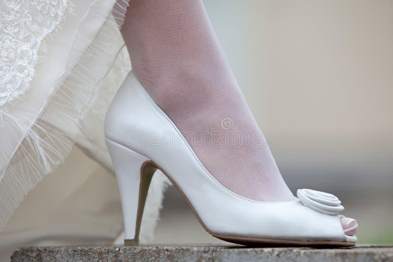 Παπούτσια και hem γυναικών του γαμήλιου φορέματος Πόδι της νύφης σε ένα άσπρο παπούτσι στοκ εικόνες